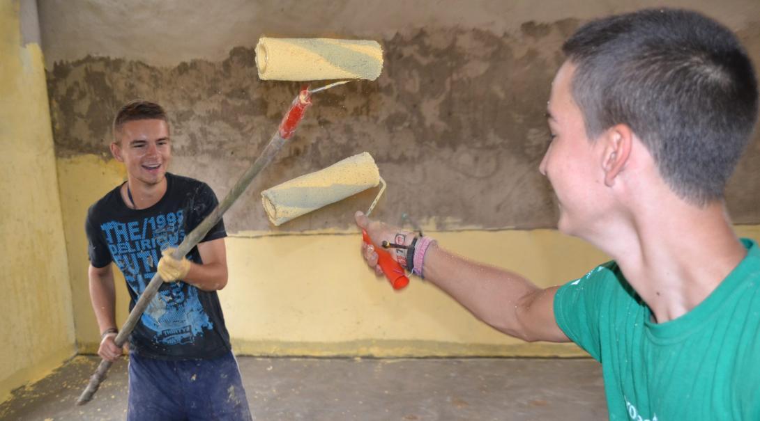 Voluntarios se divierten mientras pintan un aula en su voluntariado de construcción en Ghana.
